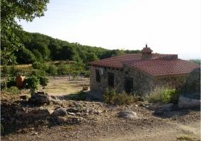 Fachada de piedra con el entorno de la casa rural