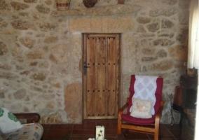 Zona de sillones, pared de piedra y puerta de madera