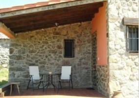 Zona de porche de piedra con mobiliario
