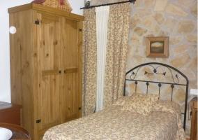 Cama individual del dormitorio doble con armario y paredes de piedra