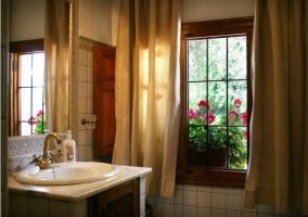 Cuarto de baño con cortinas y flores en el exterior