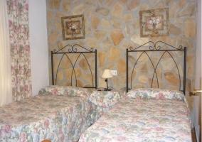 Dormitorio con dos camas individuales y paredes de piedra