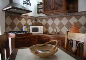 Esquina de la cocina con muebles de madera, microondas y mesa