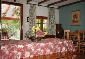 Salón-comedor con mesas, cortinas y vigas de madera