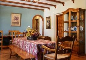 Salón-comedor con sillas, mesa, muebles y vigas de madera