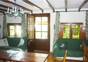 Sillones verdes con mesa y puerta. Contraventanas abiertas