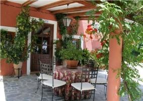 Zona de porche con mobiliario y pared roja