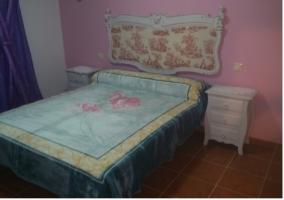 Dormitorio con cama de matrimonio y cabecero de la casa rural