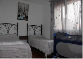 Dormitorio con dos camas de la casa rural con cuna supletoria