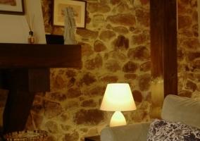 Sala de estar con paredes de piedra y cojines tapizados