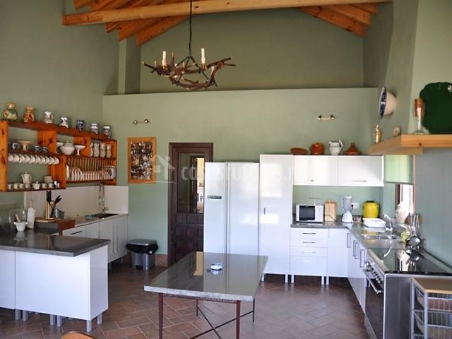 Cocina con mesa, encimeras, estanterías, y equipamiento