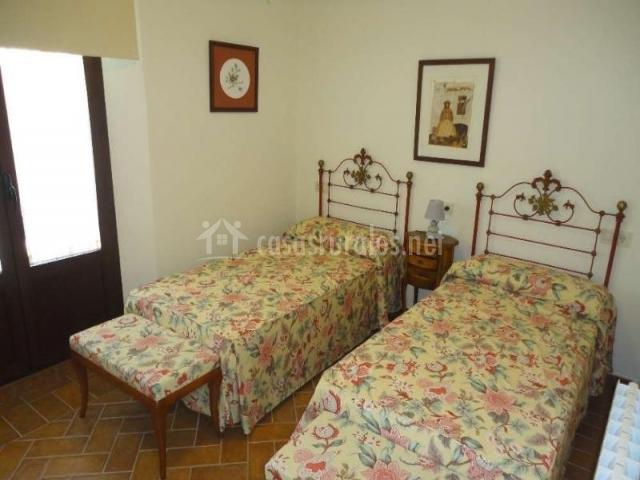 Dormitorio doble con colchas amarillas y de flores