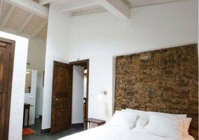 Dormitorio de matrimonio con frontal en piedra enmarcada