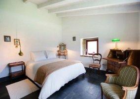 Dormitorio de matrimonio con ventana en el lateral y manta