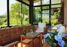 Vistas del porche acristalado con mesa de madera