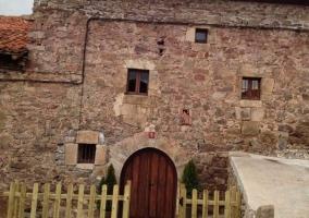 Sala de estar y comedor con chimenea y paredes de piedra