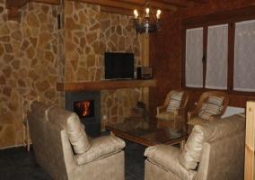 Mesa de comedor de madera junto a zona de estar con sillones