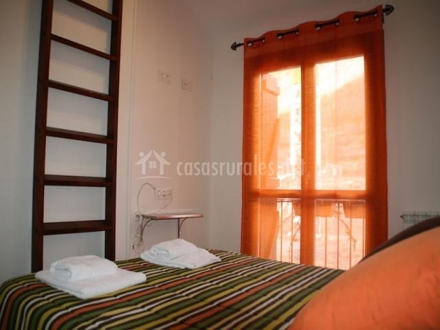 Dormitorio con cama de matrimonio, escalera y balcón