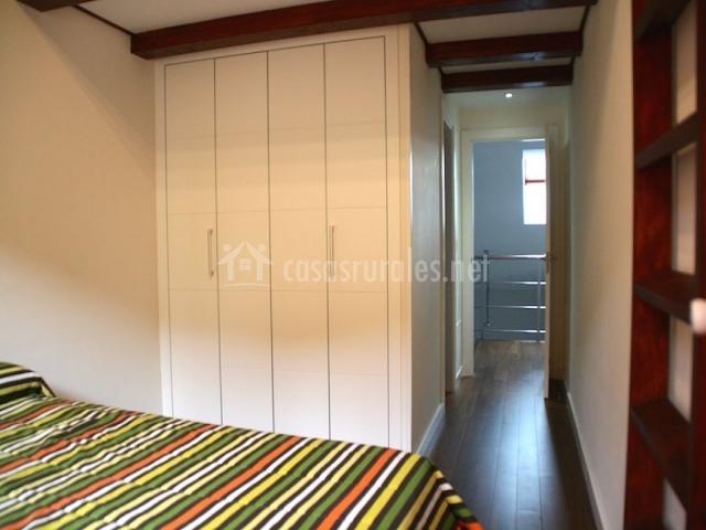 Habitación de matrimonio con escalera y armario blanco