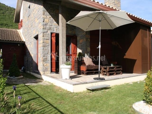 Terraza en el jardín con sombrilla y muebles