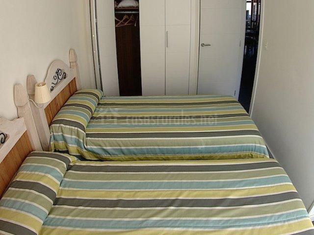 Habitación con dos camas y armarios blancos
