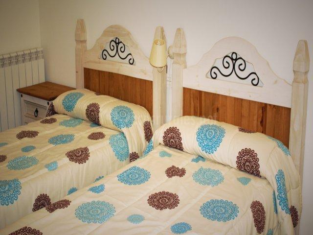 Habitación doble con cabeceros de madera marrón y blanca