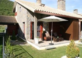 Jardín y terraza con sombrilla y muebles de madera