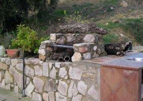 Barbacoa en el jardín bajo un muro de piedra