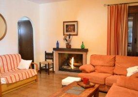 Salón con 3 sofás y una chimenea