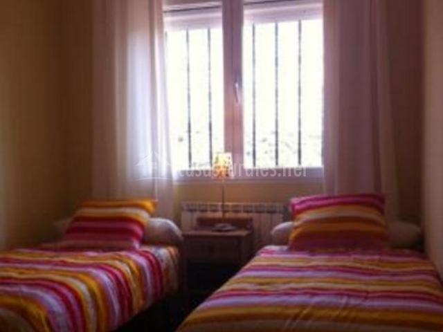 Dormitorio doble con colchas de rayas y ventana