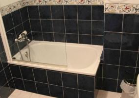Aseo con bañera y azulejos negros