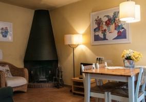 Sala de estar con chimenea en esquina y mesa para comer