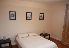 Dormitorio de matrimonio con cuadros