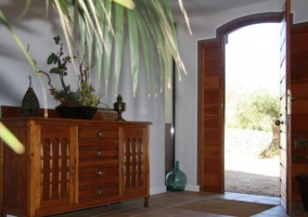 Entrada a la casa con mueble de madera y plantas