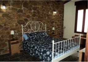 Dormitorio de matrimonio con forja blanca en la casa rural.