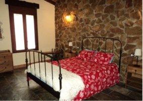 Dormitorio de matrimonio con forja negra en la casa rural.
