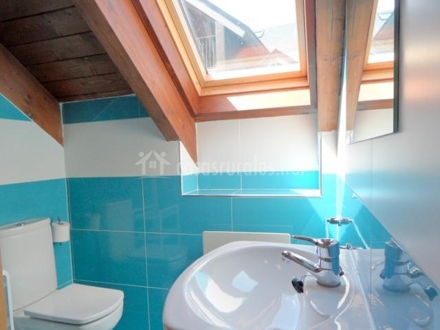 Aseo abuhardillado con azulejos azules y blancos