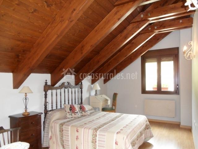 Dormitorio con cama doble y techo abuhardillado