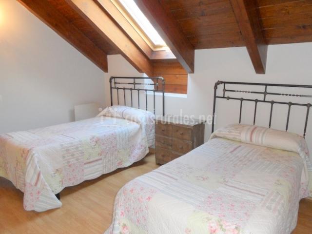 Dormitorio con dos camas y techo abuhardillado