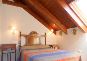 Dormitorio abuhardillado con cama de matrimonio