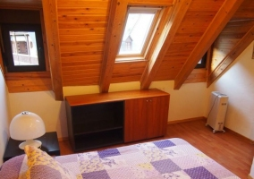 Dormitorio de matrimonio con colcha en color morado y techos de madera