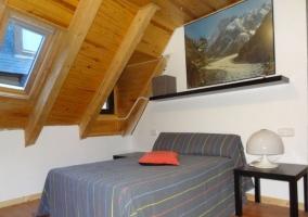 Dormitorio de matrimonio con techo de madera y un tragaluz