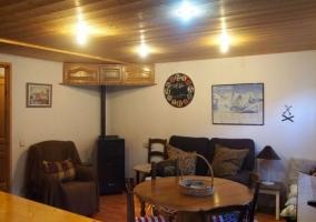 Sala de estar con mesa de madera redonda y estufa