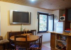 Sala de estar con mesa redonda junto a la tele