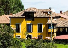 Acceso principal con fachada en color amarillo y espacios verdes