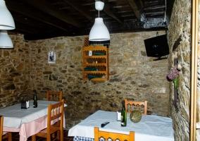 Comedor del alojamiento con varias mesas y paredes de piedra