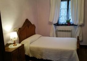Dormitorio de matrimonio con suelos de madera y colcha blanca