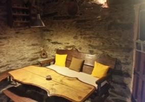 Sala de estar con la mesa de madera al lado con bancos