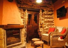 Sala de estar con sillones morados y paredes en piedra