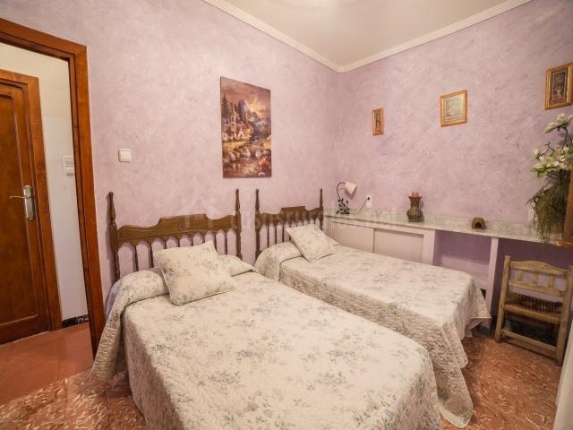 Dormitorio de matrimonio con cojín, mesillas con lámparas y armario con televisión